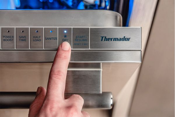 finger pressing star dry button on thermador dishwasher